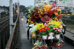 Hanoi, Vietnam A woman selling artificial flowers rides her bicycle along the Long Bien bridge