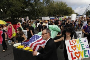 New Orleans Protesters walk beside a replica of the Statue of Liberty in a coffin during a mock jazz funeral procession