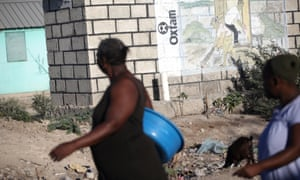 People walk past an Oxfam sign at a camp for displaced people in Haiti