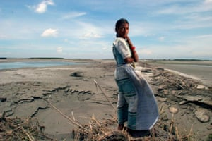 A girl standing where her house used to be. It was washed away due to heavy floods in Chawhara, Bangladesh