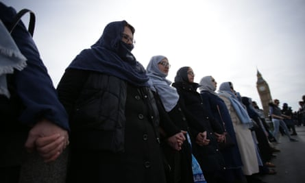 Women activists wearing blue hold hands on Westminster Bridge.
