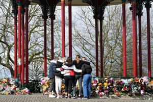 People embrace after placing flowers at the bandstand on Clapham Common.