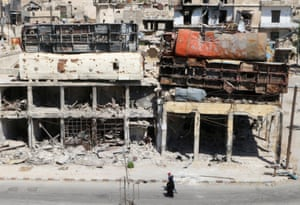 People walk past damaged buses positioned on top of buildings as barricades in the rebel-held Bab al-Hadid area