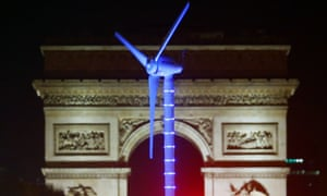A power-generating windmill turbine is seen on the Champs Elysees with the Arc de Triomphe in background.