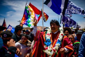 Bolivia's former president Evo Morales waves surrounded by supporters in his hometown Orinoca