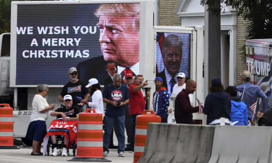 People stand by pictures of Donald Trump as his motorcade returns to Mar-a-Lago following a round of golf at the Trump International Golf Club in West Palm Beach, Florida, on Christmas Eve.
