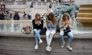 Teenage girls on their smartphones in the middle of Trafalgar Square, London