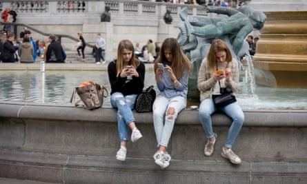 Teenage girls on their smartphones in Trafalgar Square, London.