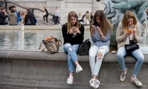 Teenagers absorbed in their smartphones in central London.
