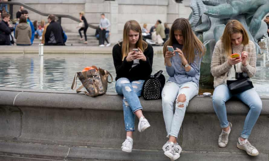 Three teenage girls are lost on their smartphones in Trafalgar Square, central London