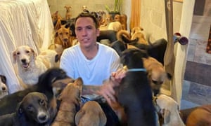 Ricardo Pimentel plays with dogs that he sheltered at his home in Leona Vicario, Mexico, during Hurricane Delta.