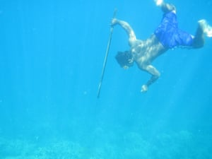 A Bajau diver hunting fish underwater using a traditional spear.