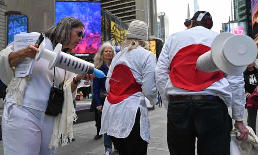 Street theater activists for health freedom simulate being injected by large Covid-19 syringes in an anti-vax protest in Times Square, New York.