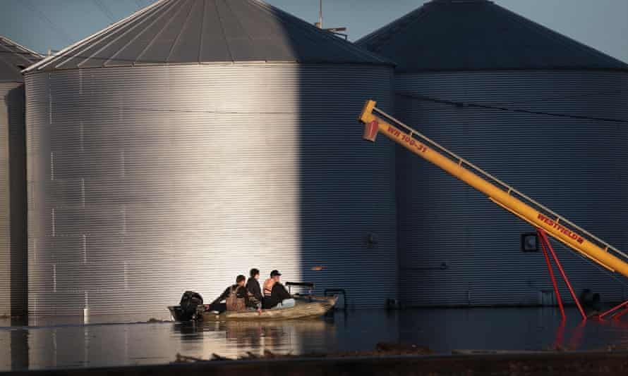 A boat passes by grain bins that are surrounded by floodwater on 21 March, in Craig, Missouri