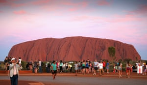 Tourists take photographs at sunset at Uluru