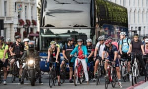 Cyclists wait at traffic lights in London.