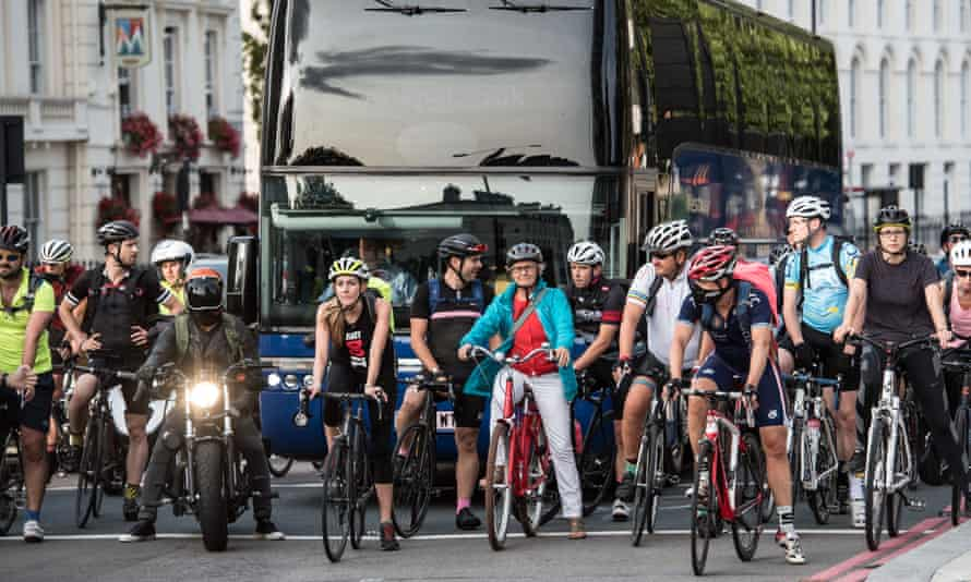 Cyclists wait at traffic lights in London, England.