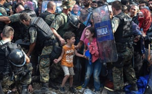 Children cry as migrants waiting on the Greek side of the border break through a cordon of Macedonian special police forces to cross into Macedonia, near the southern city of Gevgelija on 21 August 2015.