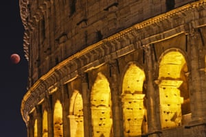 The moon appears to hang like a bauble next to the Colosseum in Rome.
