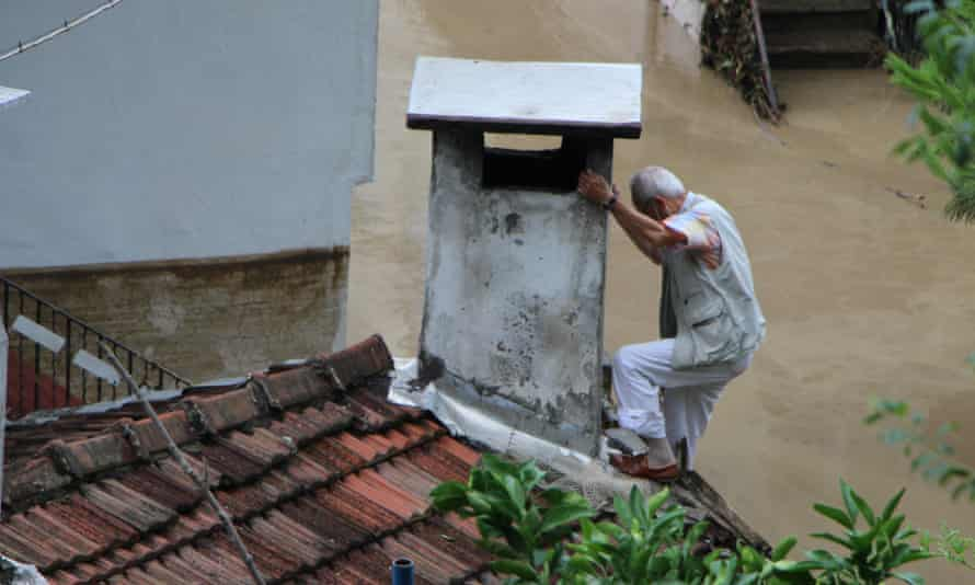 A man climbs to a chimney to rescue himself from the flood after heavy rains cause floods in Inebolu district of Kastamonu, Turkey
