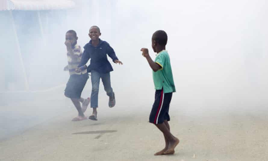 Children in the Dominican Republic running from fumes as air force personnel fumigate against the Aedes aegypti mosquito, vector of the Zika virus.
