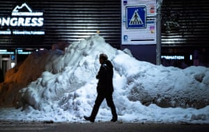 A man walks past a pile of snow in the town centre of Berchtesgaden, Bavaria, Germany.