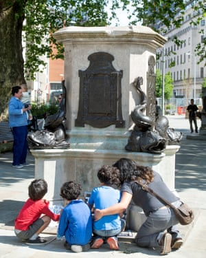 A family read messages placed around the plinth at the site of the toppled statue of Edward Colston.