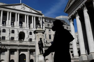 FILE PHOTO: The spread of the coronavirus disease (COVID-19) in LondonFILE PHOTO: A person wearing a mask walks past the Bank of England, as the spread of the coronavirus disease (COVID-19) continues, in London, Britain, March 23, 2020. REUTERS/Toby Melville/File Photo