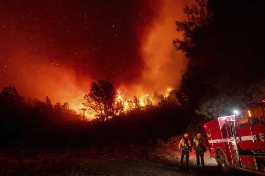 Firefighters watch the Bear fire, a smaller blaze that became part of the North Complex fire, approach in Oroville, California, on 9 September.