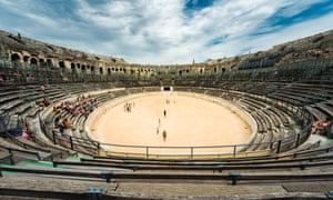 Inside historical Nimes arena. Some tourists walking around.