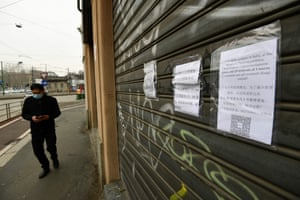 A man wearing a respiratory mask checks his smartphone next to a closed store in the Chinese district of Milan.