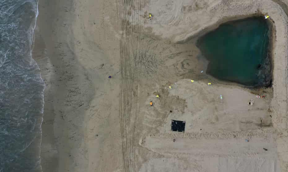 Crews clean up oil in a pool that flowed in from the high tide and was held back by a sand berm and boom, on the border of Huntington Beach and Newport Beach on Monday.