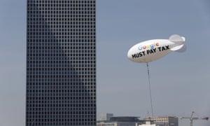 """Blimp reading """"Google must pay tax"""" floating over the Tel Aviv skyline"""