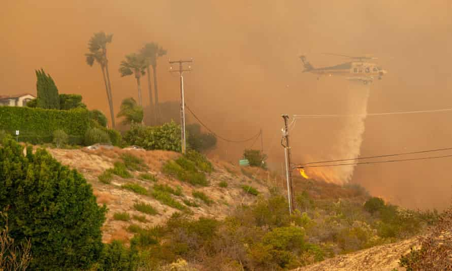 A Los Angeles County Fire Department Sikorsky S-70 Firehawk helicopter works to save a home from the encroaching flames of the Woolsey Fire.