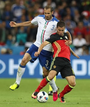 Giorgio Chiellini takes the punishment of a booking for holding back Hazard.