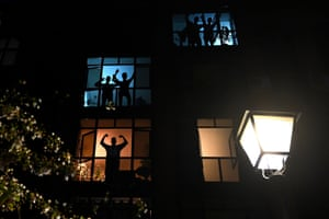 Neighbours in a residential building gesture and applaud from their windows to pay tribute to healthcare workers