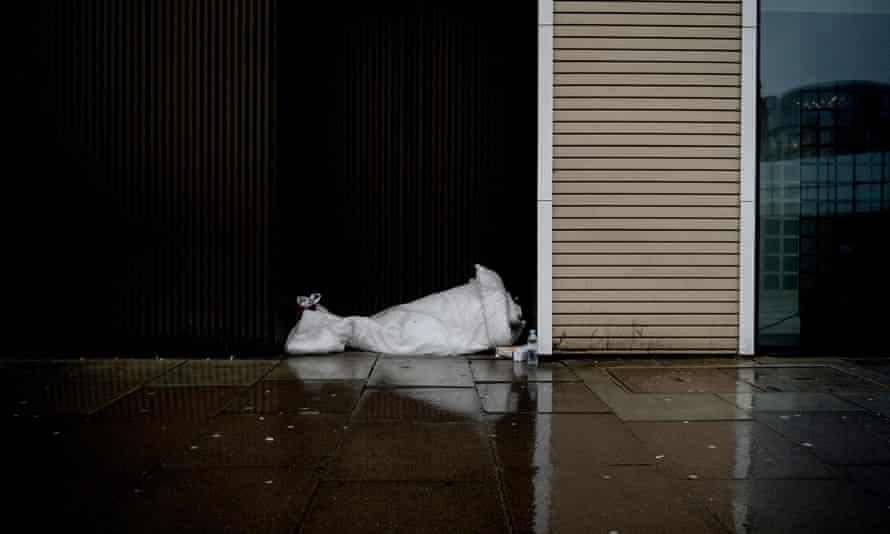 A homeless man lies in a sleeping bag in London