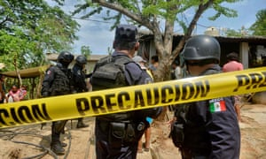 Police outside the house where were six people – including a four-month-old baby – were killed by gunmen in San Pedro Cacahuatepec near Acapulco.