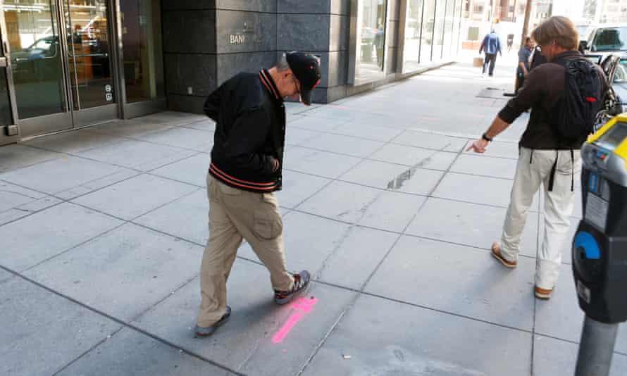 Pedestrians inspect cracks near the sinking Millennium Tower in San Francisco.