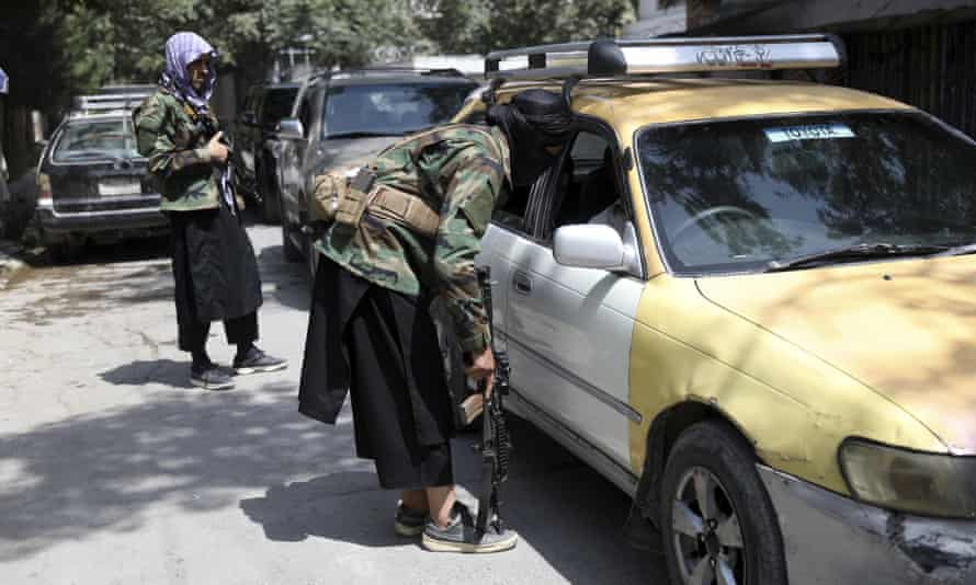 Taliban fighters search a vehicle at a checkpoint on the road in the Wazir Akbar Khan area of Kabul, Afghanistan, on Sunday.
