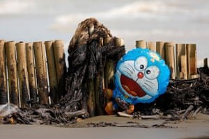Karawang, Indonesia: A balloon depicting the Japanese manga character Doraemon is stranded on a bamboo fence at a beach covered with oil from a recent spill