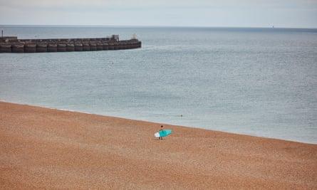 A single surfer on Brighton beach on 16 July 2020