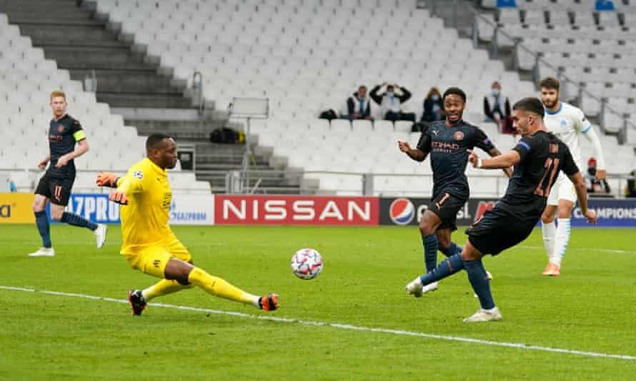 Ferran Torres shoots past Steve Mandanda to score for Manchester City against Marseille.