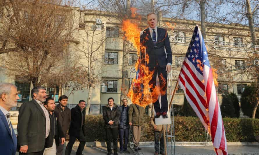 A cardboard cutout of Rob Macaire is burned alongside British and US flags during a memorial for victims of the Ukraine plane crash at the University of Tehran