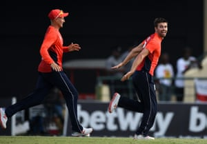 Mark Wood of England celebrates with Joe Root after dismissing Nicholas Pooran of the West Indies