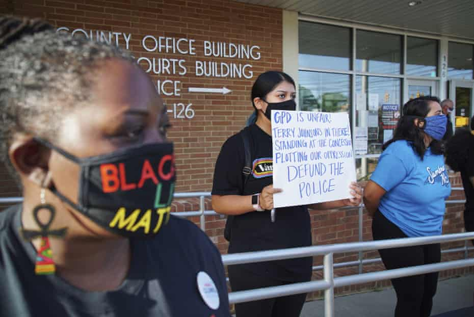 Aranza Sosa, center, holds a sign at a protest in front of the Alamance county government building in Graham, North Carolina, on 3 August. Sosa, who was born in Mexico and is now a U.S. citizen, says the county is a hostile place for people of color.