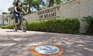 A cyclist rides by the entrance to the University of Miami.