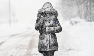 A woman struggles in the snow and wind