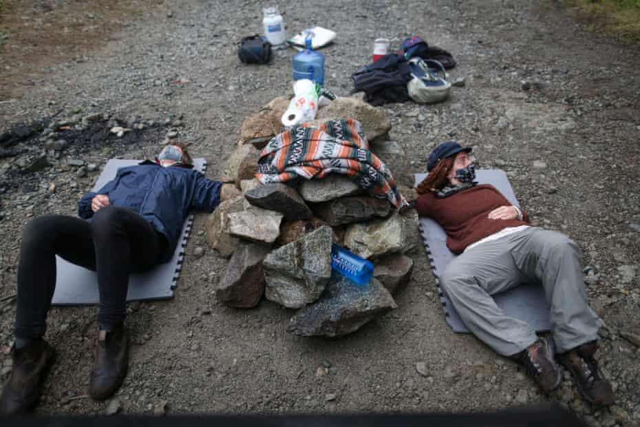 Two protesters lie on a logging road with their arms chained inside a device cemented into the ground.