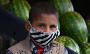 A young street vendor in Kabul wearing a face mask